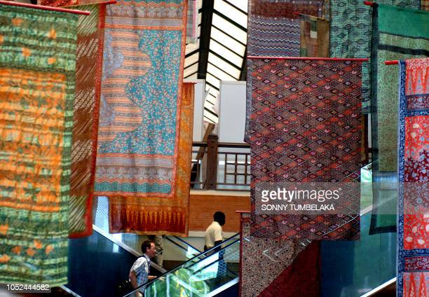Delegates pass by batiks displayed as a decoration at the UN Climate Change Conference 2007 venue in Nusa Dua on Bali island 07 December 2007 In the...