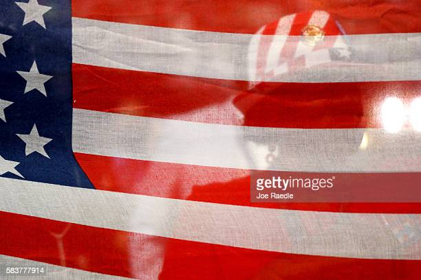 Delegates raise an American flag during the opening of the third day of the Democratic National Convention at the Wells Fargo Center July 27 2016 in...