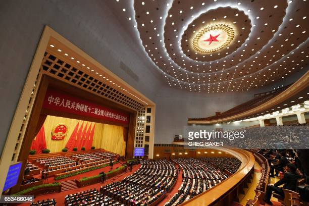 Delegates sit through the closing session of the National People's Congress China's legislature in Beijing's Great Hall of the People on March 15...