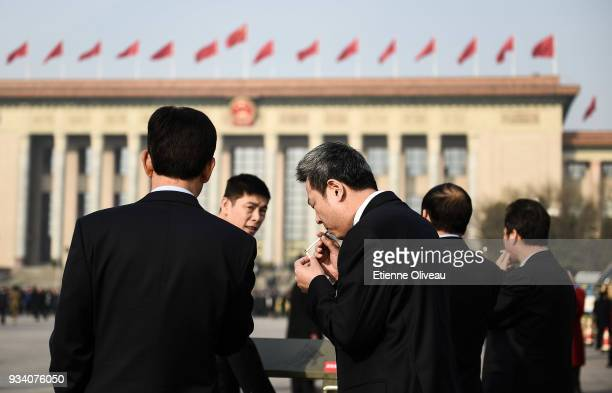 Delegates smoke a cigarette on Tiananmen Square before the seventh plenary session of the 13th National People's Congress at the Great Hall of the...
