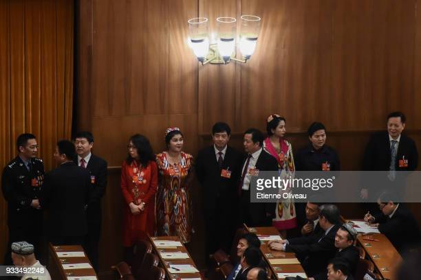 Delegates stand after casting their ballots during the sixth plenary session of the National People's Congress at the Great Hall of the People on...