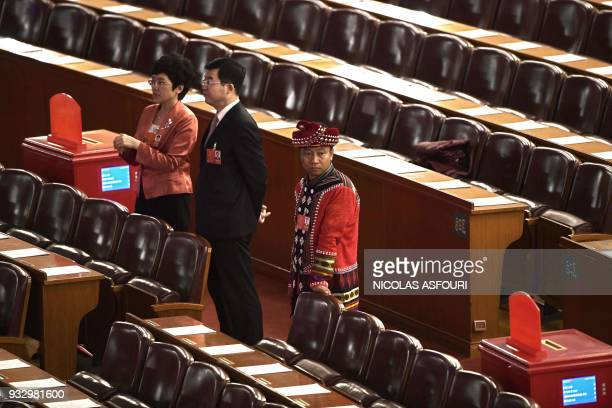 Delegates stand ahead of the fifth plenary session of the first session of the 13th National People's Congress at the Great Hall of the People in...