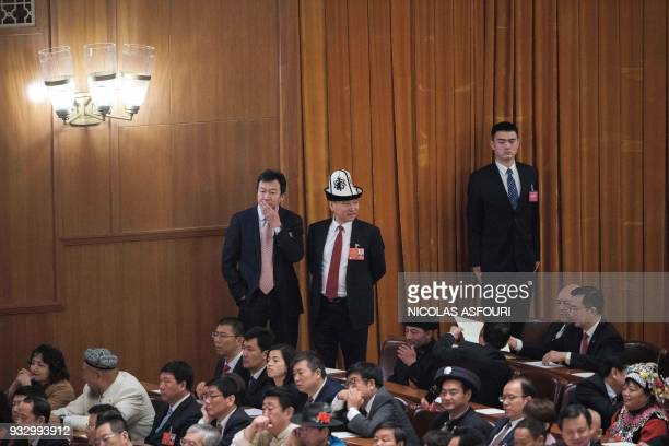 Delegates stand and sit during the fifth plenary session of the first session of the 13th National People's Congress at the Great Hall of the People...