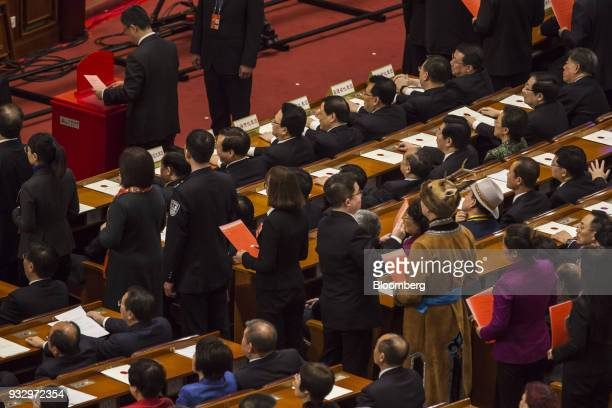 Delegates stand in line to cast their ballots during a vote at a session at the first session of the 13th National People's Congress at the Great...