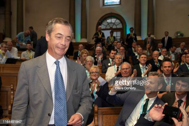 Delegates take photographs of Brexit Party leader Nigel Farage as he arrives to addresses party members and delegates at an event to introduce...