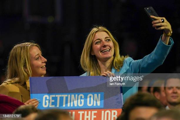 Delegates take selfies as they wait to listen to Prime Minister Boris Johnson's keynote speech during the Conservative Party conference at Manchester...