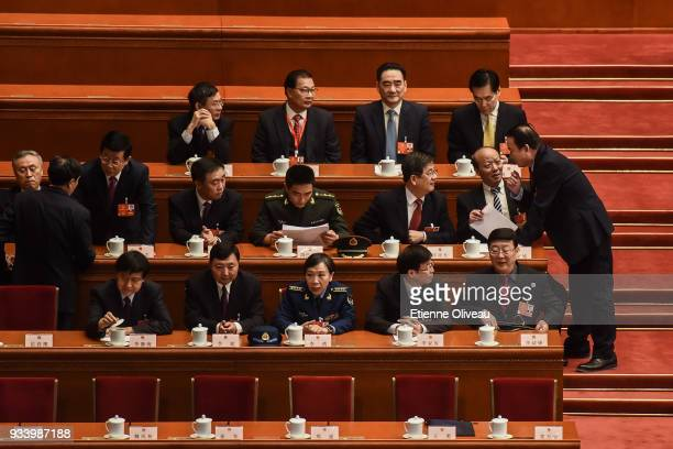 Delegates talk before the seventh plenary session of the 13th National People's Congress at the Great Hall of the People on March 19, 2018 in...