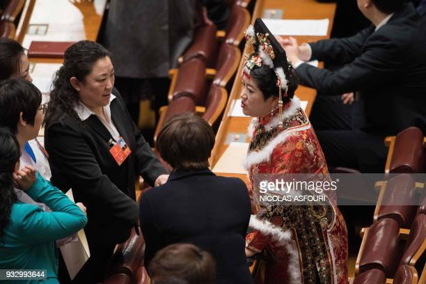 Delegates talk during the fifth plenary session of the first session of the 13th National People's Congress at the Great Hall of the People in...
