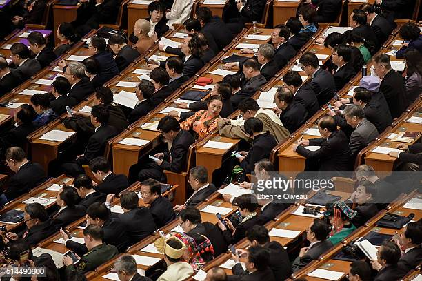 Delegates wait for the beginning of the Second Plenary Meeting inside the main meeting hall of the Great Hall of the People on March 9, 2016 in...