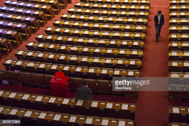 Delegates walk and stand ahead of a session during the first session of the 13th National People's Congress at the Great Hall of the People in...