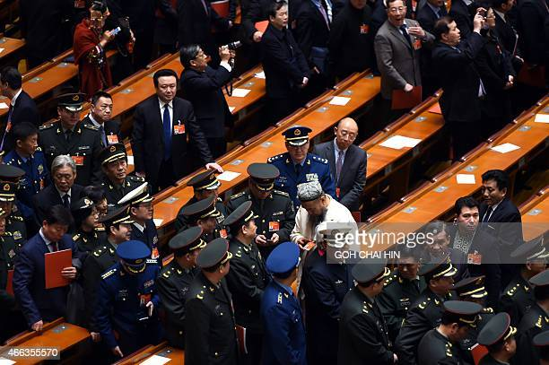 Delegates walk out after the closing of the 3rd Session of the 12th National People's Congress at the Great Hall of the People in Beijing on March 15...