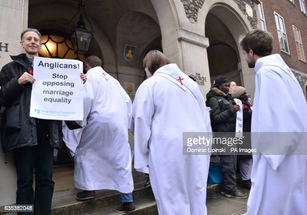 Delegates walk past Peter Tatchell and other activists from the Lesbian and Gay Christian Movement outside the General Synod at Church House in...