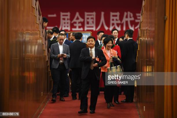 Delegates walk through an entrance before the closing session of the National People's Congress China's legislature in Beijing's Great Hall of the...