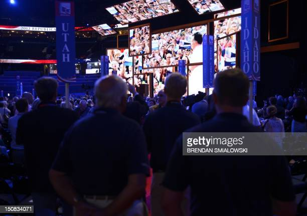 Delegates watch campaign videos of presidential candidate Mitt Romney after the chairman of the Republican National Convention Reince Priebus gaveled...