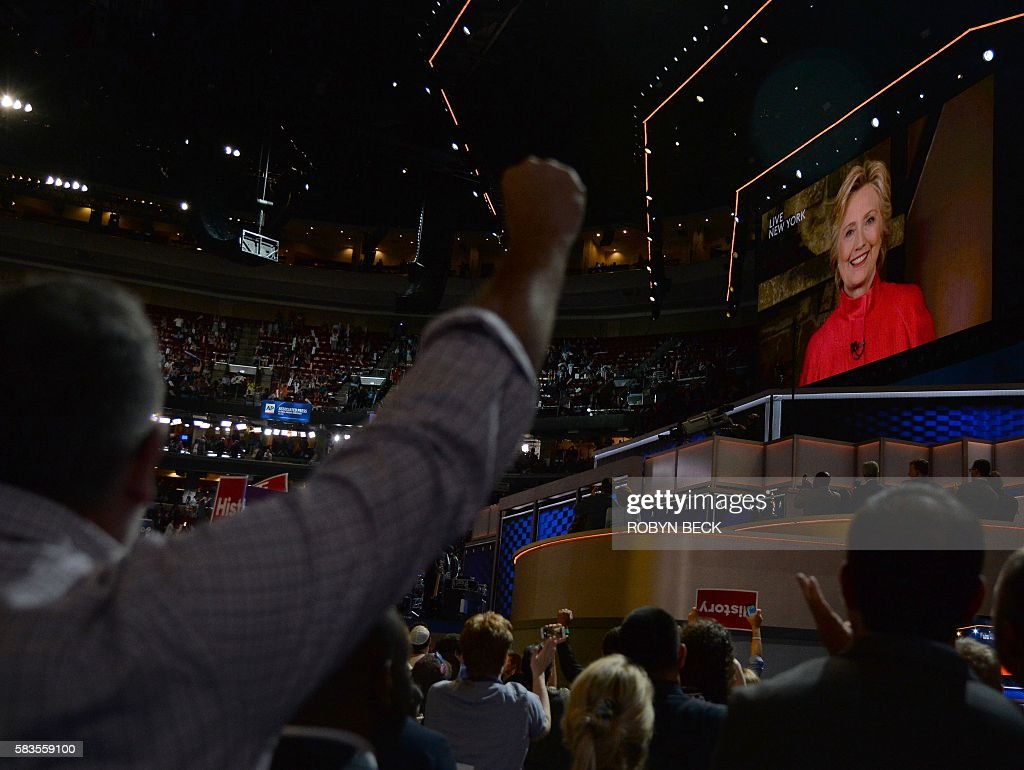 Delegates watch Hillary Clinton speak live from New York during Day 2 of the Democratic National Convention at the Wells Fargo Center, July 26, 2016 in Philadelphia, Pennsylvania. / AFP / Robyn BECK