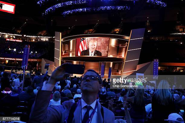 Delegates watch Republican presidential candidate Donald Trump speak on a screen from New York City on the second day of the Republican National...