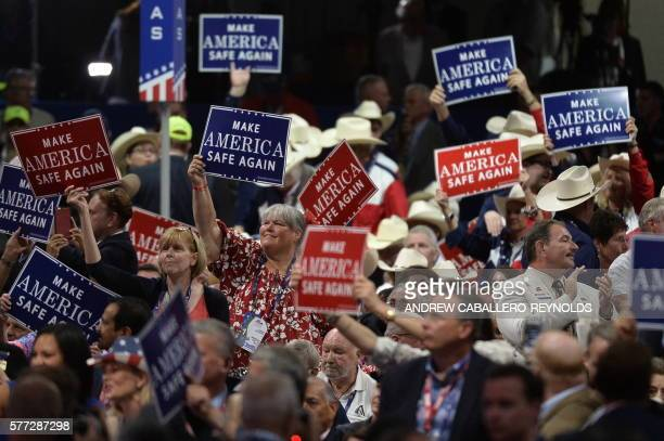 TOPSHOT Delegates wave signs on the first day of the Republican National Convention on July 18 2016 at the Quicken Loans Arena in Cleveland Ohio The...