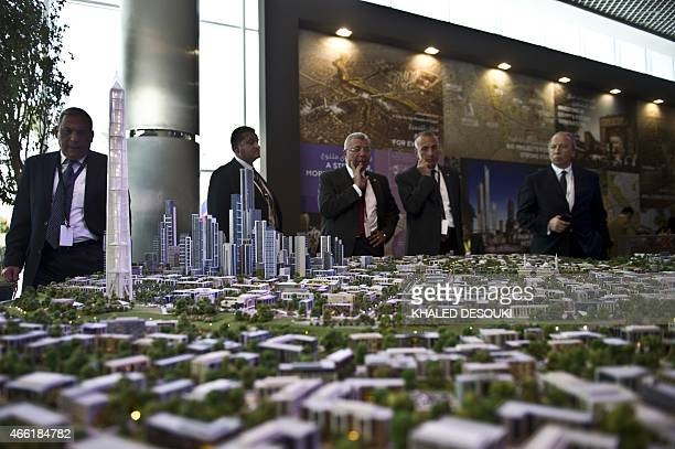 A delegation looks at a scale model of the new Egyptian capital displayed at the congress hall in the Red Sea resort of Sharm elSheikh on March 14...