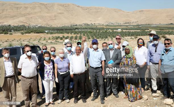 A delegation made up of European and British diplomats as well as members of development institutions pose for a picture with residents of the Jordan...