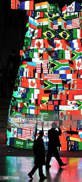 Delegation officials pass a screen tower displaying the flags of the G20 member countries at the Seoul international convention and venue of the G20...