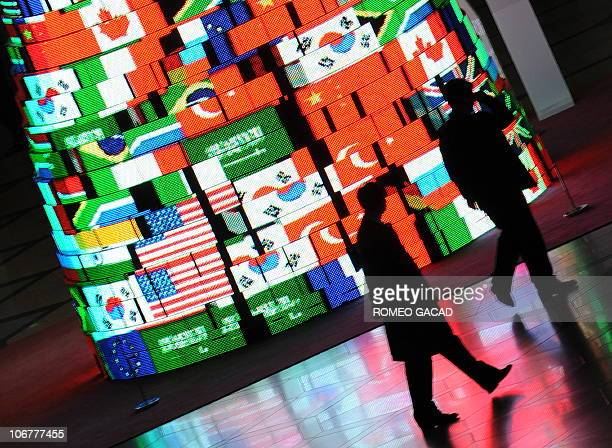 Delegation officials walk past a screen tower displaying the flags of the G20 member countries at the Seoul international convention and venue of the...
