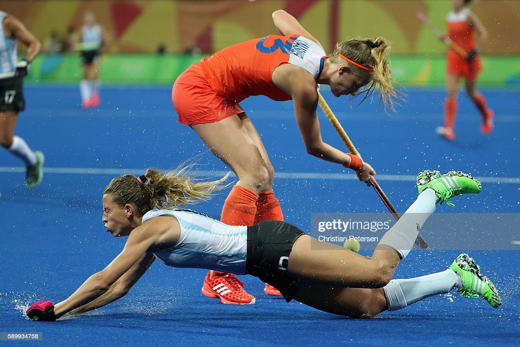 Delfina Merino #12 of Argentina falls as she attempts to defend Xan de Waard #3 of Netherlands during the quarter final hockey game on Day 10 of the Rio 2016 Olympic Games at the Olympic Hockey Centre on August 15, 2016 in Rio de Janeiro, Brazil.