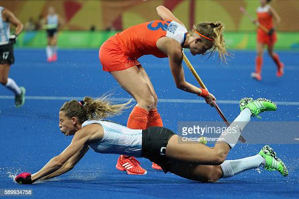 Delfina Merino of Argentina falls as she attempts to defend Xan de Waard of Netherlands during the quarter final hockey game on Day 10 of the Rio...