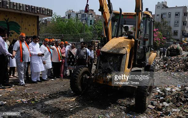 Delhi BJP chief Satish Upadhyay BJP party workers and MCD workers cleaning a dust bin after sanitation workers in east and north Delhi called off...