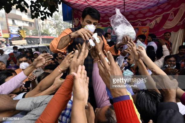 Delhi BJP President Manoj Tiwari distributing Air Mask to public at Durga Puri Chowk at Sahadra on November 10 2017 in New Delhi India
