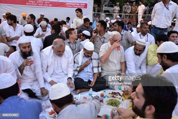 Delhi Chief Minister Arvind Kejriwal along with AAP MLA Amanatullah Khan during an Iftar party at Ansari Auditorium in Jamia Milia University on June...