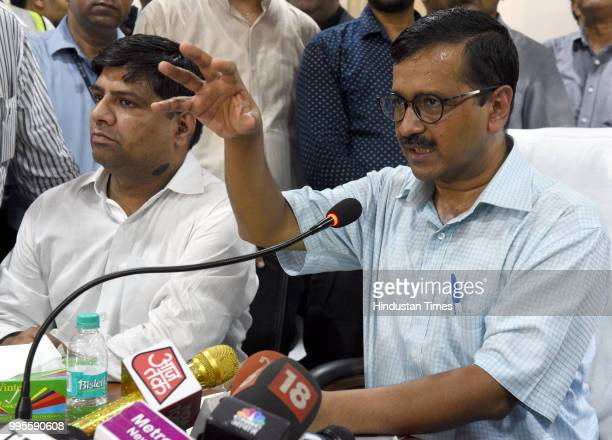 Delhi Chief Minister Arvind Kejriwal speaks as AAP MLA and ViceChairman of Delhi Jal Board Dinesh Mohaniya looks on during a press conference after...