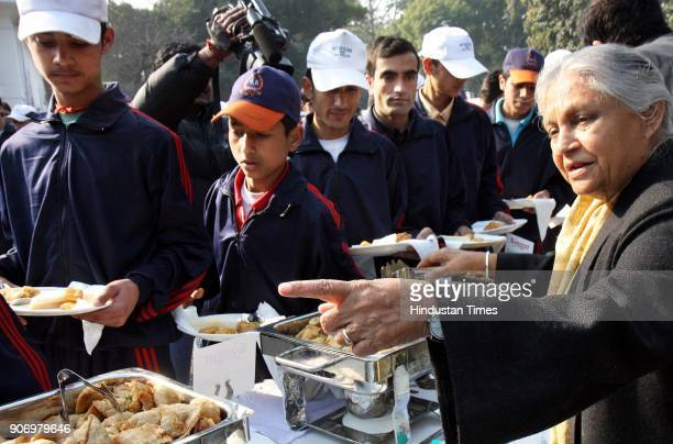 Delhi CM Sheila Dikshit serves food to school children from the remote area of Jammu Kashmir at her residence in New Delhi on Saturday