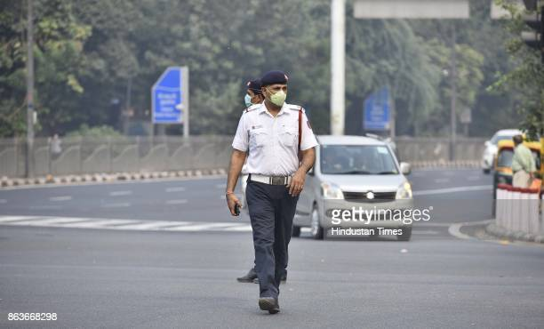 Delhi cops wear masks while managing traffic at ITO as thick smog and pollution covered the roads a day after Diwali on October 19 2017 in New Delhi...