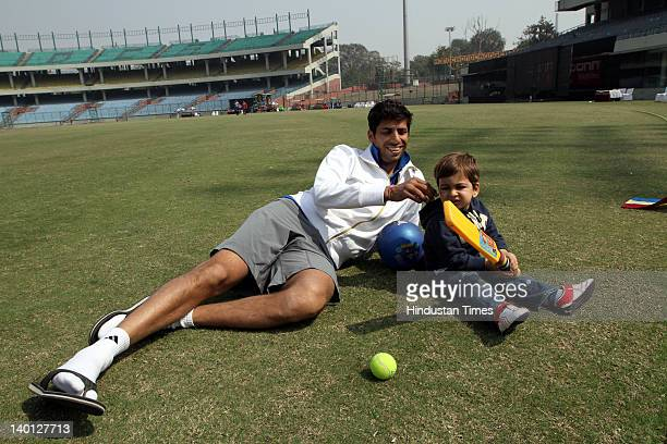 Delhi cricket player Ashish Nehra plays with his son Arush at Ferozshah Kotla Ground during Vijay Hazare Trophy one day match between Delhi and...