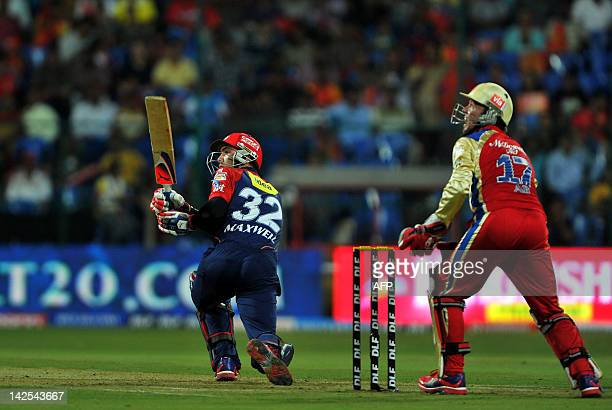 Delhi Daredevils batsman Glenn Maxwell is watched by Royal Challengers Bangalore wicketkeeper A B DeVilliers as he plays a stroke during the IPL...