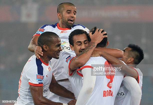 Delhi Dynamos FC forward Robin Singh celebrates with teammates after scoring during the first leg of the semifinal football match between Delhi...
