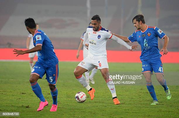 Delhi Dynamos FC forward Robin Singh plays against FC Goa's Indian defender Narayan Das and FC Goa's Brazilian midfielder Jonatan Lucca during the...