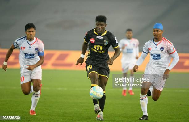 Delhi Dynamos FC player Rowilson Rodrigues and Pritam Kotal vies for the ball with with Kerala Blaster player Courage Pekuson during the Hero ISL...
