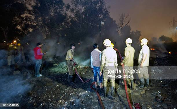 Delhi Fire Service personnel extinguish a fire in New Delhi on November 11 2013 Slum huts were gutted in a fire which broke out in the evening near...