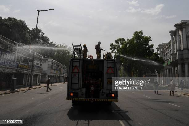 Delhi Fire Service personnel spray disinfectant chemicals along a road during a government-imposed nationwide lockdown as a preventive measure...