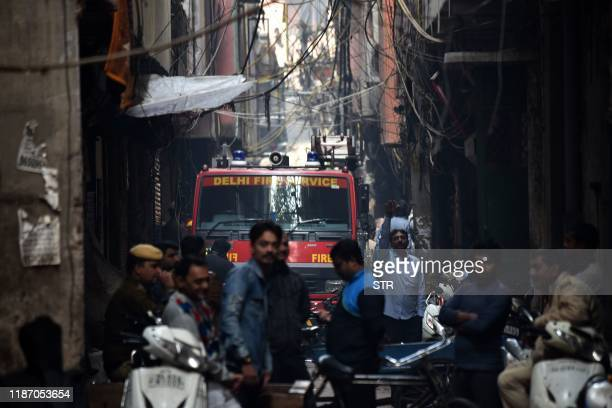 Delhi Fire Service truck is seen along a street near the site of a factory where a fire broke out, in Anaj Mandi area of New Delhi on December 8,...