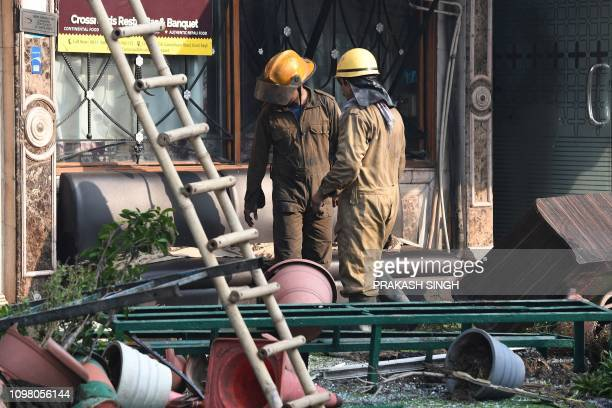 Delhi Fire Services personnel stand outside Hotel Arpit Palace after extinguishing a fire that broke out on its premises in New Delhi on February 12...