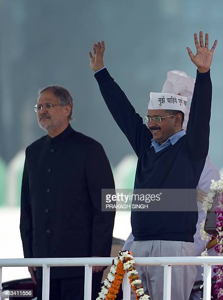 Delhi Lieutenant Governor Najib Jung watches aS Aam Aadmi Party president Arvind Kejriwal greets his supporters during his swearingin ceremony as...