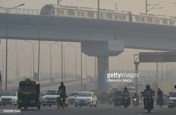 A Delhi metro train runs on a track above vehicles amid heavy smog conditions in New Delhi on October 30 2018 Smog levels spike during winter in...