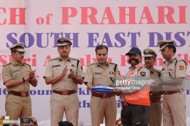 Delhi Police Commissioner Amulya Patnaik awarding a security guard during the launch of Community Policing Scheme Prahari by Delhi Police in...