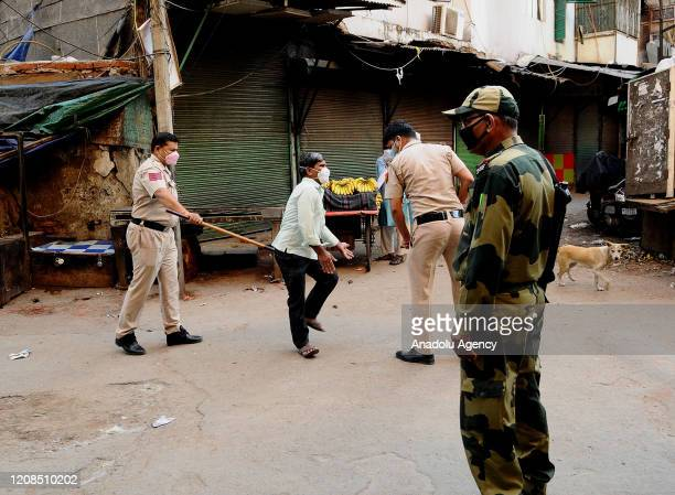 Delhi police officer wields his baton against a man as a punishment for breaking the lockdown rules after India ordered a 21-day nationwide lockdown...