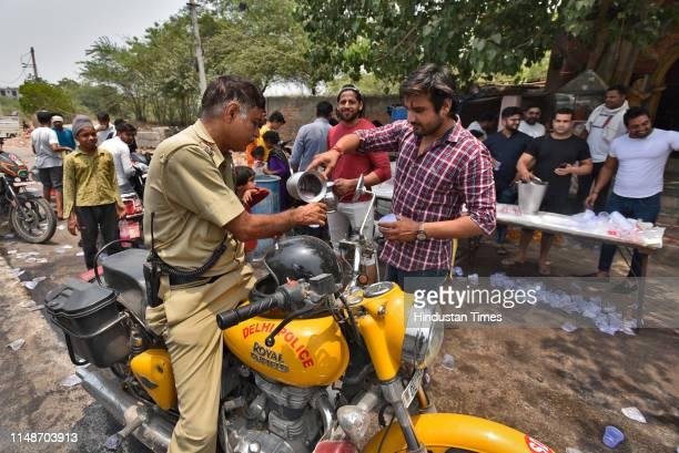 Delhi police personnel drinks flavored water, distributed by local residents as a goodwill gesture on a summer day, at Chattarpur, on June 9, 2019 in...