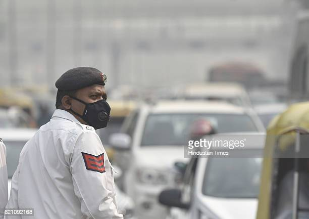Delhi Police personnel manage traffic and covers himself with his mask to avoid thick smog at ITO as city covered under a blanket of heavy smog air...