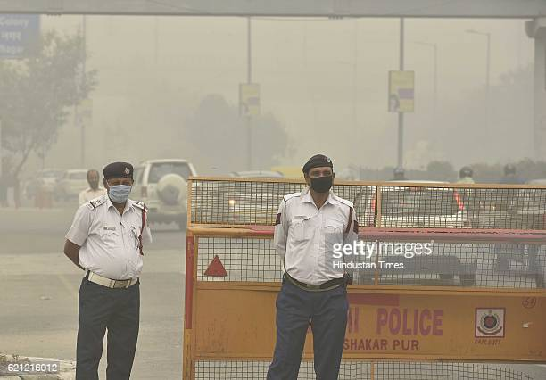 Delhi Police personnel manage traffic and covers himself with his mask to avoid thick smog at Near Akshardham Temple as the whole city is engulfed in...