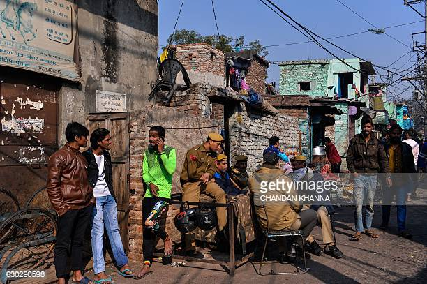 Delhi police personnel sit at a corner in the Kathputli Colony in New Delhi on December 20 2016 The name Kathputli Colony comes from the Hindi word...